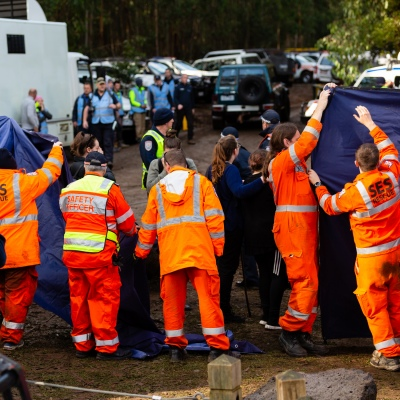 SES volunteers hold up tarpaulins as media wait for William to arrive at the staging area at Mt Disappointment in Victoria. An air-and-ground search is continuing for lost Victorian teenager William Callaghan, who suffers from non-verbal autism and is lost in steep and rugged terrain in Victoria after temperatures dropped below freezing overnight.
