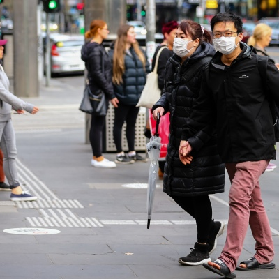 MELBOURNE, AUSTRALIA - June 21: A couple wearing facemasks are seen walking in the CBD as restrictions are being tightened in Victoria during COVID 19 on 21 June, 2020 in Melbourne, Australia. After a concerning spike in new coronavirus infections in metropolitan Melbourne which is once again sparking fears of a second wave, the Premier Daniel Andrews announced yesterday (20 June) that restrictions on the number of visitors in private homes will be reduced to ten to five. Victoria recorded 19 new cases overnight, the fifth day in a row of double digits increases, prompting the Government to extend the State of Emergency for another four weeks giving Police unprecedented powers to enforce directions managed by the State Government. It includes three new cases linked to an outbreak among contractors working at the Samford Plaza Hotel. The State was in the midst of easing restrictions allowing restaurants, bars and cafes to increase the number of inside patrons from 20 to 50. As a result of this spike, the Government has reversed in decision to further ease restrictions on hospitality businesses forcing many to shut their doors forever. Some of Melbourne's most well-known restaurateurs are at on the brink of permanent closure. Victoria has had the strictest Coronavirus restrictions in the country, yet is by far the worst performing state, raising questions over the real effectiveness of this strategy. (Photo by Speed Media/Icon Sportswire)