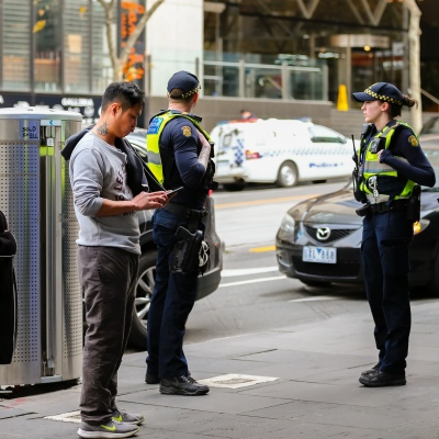 MELBOURNE, AUSTRALIA - June 21: Police are seen talking to a man and a women in the CBD as restrictions are being tightened in Victoria during COVID 19 on 21 June, 2020 in Melbourne, Australia. After a concerning spike in new coronavirus infections in metropolitan Melbourne which is once again sparking fears of a second wave, the Premier Daniel Andrews announced yesterday (20 June) that restrictions on the number of visitors in private homes will be reduced to ten to five. Victoria recorded 19 new cases overnight, the fifth day in a row of double digits increases, prompting the Government to extend the State of Emergency for another four weeks giving Police unprecedented powers to enforce directions managed by the State Government. It includes three new cases linked to an outbreak among contractors working at the Samford Plaza Hotel. The State was in the midst of easing restrictions allowing restaurants, bars and cafes to increase the number of inside patrons from 20 to 50. As a result of this spike, the Government has reversed in decision to further ease restrictions on hospitality businesses forcing many to shut their doors forever. Some of Melbourne's most well-known restaurateurs are at on the brink of permanent closure. Victoria has had the strictest Coronavirus restrictions in the country, yet is by far the worst performing state, raising questions over the real effectiveness of this strategy. (Photo by Speed Media/Icon Sportswire)