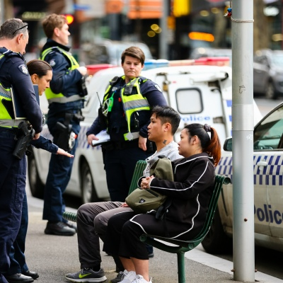 MELBOURNE, AUSTRALIA - June 21: A large group of police question a man and a woman in the CBD as restrictions are being tightened in Victoria during COVID 19 on 21 June, 2020 in Melbourne, Australia. After a concerning spike in new coronavirus infections in metropolitan Melbourne which is once again sparking fears of a second wave, the Premier Daniel Andrews announced yesterday (20 June) that restrictions on the number of visitors in private homes will be reduced to ten to five. Victoria recorded 19 new cases overnight, the fifth day in a row of double digits increases, prompting the Government to extend the State of Emergency for another four weeks giving Police unprecedented powers to enforce directions managed by the State Government. It includes three new cases linked to an outbreak among contractors working at the Samford Plaza Hotel. The State was in the midst of easing restrictions allowing restaurants, bars and cafes to increase the number of inside patrons from 20 to 50. As a result of this spike, the Government has reversed in decision to further ease restrictions on hospitality businesses forcing many to shut their doors forever. Some of Melbourne's most well-known restaurateurs are at on the brink of permanent closure. Victoria has had the strictest Coronavirus restrictions in the country, yet is by far the worst performing state, raising questions over the real effectiveness of this strategy. (Photo by Speed Media/Icon Sportswire)