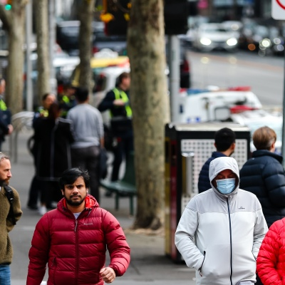 MELBOURNE, AUSTRALIA - June 21: A man and a woman are seen crossing the street wearing a facemask in the CBD as restrictions are being tightened in Victoria during COVID 19 on 21 June, 2020 in Melbourne, Australia. After a concerning spike in new coronavirus infections in metropolitan Melbourne which is once again sparking fears of a second wave, the Premier Daniel Andrews announced yesterday (20 June) that restrictions on the number of visitors in private homes will be reduced to ten to five. Victoria recorded 19 new cases overnight, the fifth day in a row of double digits increases, prompting the Government to extend the State of Emergency for another four weeks giving Police unprecedented powers to enforce directions managed by the State Government. It includes three new cases linked to an outbreak among contractors working at the Samford Plaza Hotel. The State was in the midst of easing restrictions allowing restaurants, bars and cafes to increase the number of inside patrons from 20 to 50. As a result of this spike, the Government has reversed in decision to further ease restrictions on hospitality businesses forcing many to shut their doors forever. Some of Melbourne's most well-known restaurateurs are at on the brink of permanent closure. Victoria has had the strictest Coronavirus restrictions in the country, yet is by far the worst performing state, raising questions over the real effectiveness of this strategy. (Photo by Speed Media/Icon Sportswire)
