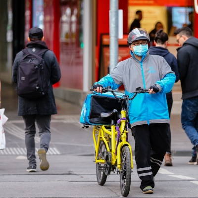 MELBOURNE, AUSTRALIA - June 21: A food delivery rider is seen wearing a facemask as he walks his bicycle across an intersection in Melbourne as restrictions are being tightened in Victoria during COVID 19 on 21 June, 2020 in Melbourne, Australia. After a concerning spike in new coronavirus infections in metropolitan Melbourne which is once again sparking fears of a second wave, the Premier Daniel Andrews announced yesterday (20 June) that restrictions on the number of visitors in private homes will be reduced to ten to five. Victoria recorded 19 new cases overnight, the fifth day in a row of double digits increases, prompting the Government to extend the State of Emergency for another four weeks giving Police unprecedented powers to enforce directions managed by the State Government. It includes three new cases linked to an outbreak among contractors working at the Samford Plaza Hotel. The State was in the midst of easing restrictions allowing restaurants, bars and cafes to increase the number of inside patrons from 20 to 50. As a result of this spike, the Government has reversed in decision to further ease restrictions on hospitality businesses forcing many to shut their doors forever. Some of Melbourne's most well-known restaurateurs are at on the brink of permanent closure. Victoria has had the strictest Coronavirus restrictions in the country, yet is by far the worst performing state, raising questions over the real effectiveness of this strategy. (Photo by Speed Media/Icon Sportswire)