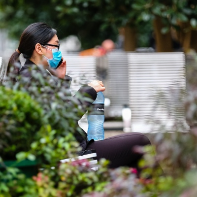 MELBOURNE, AUSTRALIA - June 21: A woman is seen wearing a facemask and talking in her phone as she sits on a bench in Bourke Street as restrictions are being tightened in Victoria during COVID 19 on 21 June, 2020 in Melbourne, Australia. After a concerning spike in new coronavirus infections in metropolitan Melbourne which is once again sparking fears of a second wave, the Premier Daniel Andrews announced yesterday (20 June) that restrictions on the number of visitors in private homes will be reduced to ten to five. Victoria recorded 19 new cases overnight, the fifth day in a row of double digits increases, prompting the Government to extend the State of Emergency for another four weeks giving Police unprecedented powers to enforce directions managed by the State Government. It includes three new cases linked to an outbreak among contractors working at the Samford Plaza Hotel. The State was in the midst of easing restrictions allowing restaurants, bars and cafes to increase the number of inside patrons from 20 to 50. As a result of this spike, the Government has reversed in decision to further ease restrictions on hospitality businesses forcing many to shut their doors forever. Some of Melbourne's most well-known restaurateurs are at on the brink of permanent closure. Victoria has had the strictest Coronavirus restrictions in the country, yet is by far the worst performing state, raising questions over the real effectiveness of this strategy. (Photo by Speed Media/Icon Sportswire)