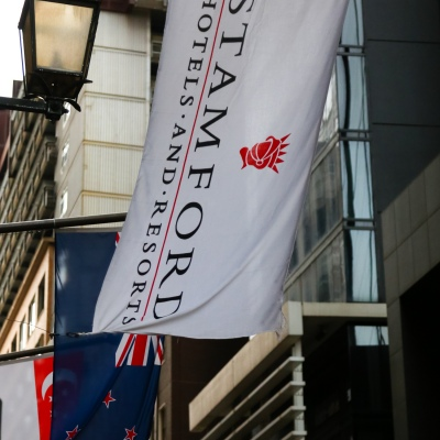 MELBOURNE, AUSTRALIA - June 21: A view of the flags above the main entrance of the Stamford Plaza Hotel where a major Coronavirus Cluster has been identified amongst contractors working there as restrictions are being tightened in Victoria during COVID 19 on 21 June, 2020 in Melbourne, Australia. After a concerning spike in new coronavirus infections in metropolitan Melbourne which is once again sparking fears of a second wave, the Premier Daniel Andrews announced yesterday (20 June) that restrictions on the number of visitors in private homes will be reduced to ten to five. Victoria recorded 19 new cases overnight, the fifth day in a row of double digits increases, prompting the Government to extend the State of Emergency for another four weeks giving Police unprecedented powers to enforce directions managed by the State Government. It includes three new cases linked to an outbreak among contractors working at the Samford Plaza Hotel. The State was in the midst of easing restrictions allowing restaurants, bars and cafes to increase the number of inside patrons from 20 to 50. As a result of this spike, the Government has reversed in decision to further ease restrictions on hospitality businesses forcing many to shut their doors forever. Some of Melbourne's most well-known restaurateurs are at on the brink of permanent closure. Victoria has had the strictest Coronavirus restrictions in the country, yet is by far the worst performing state, raising questions over the real effectiveness of this strategy. (Photo by Speed Media/Icon Sportswire)