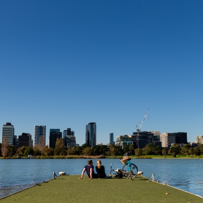MELBOURNE, AUSTRALIA - MAY 16: A young couple laugh and enjoy the perfect weather as they sit on a pier with their bicycles at Albert Park Lake as restrictions are being eased in Victoria during COVID 19 on 16 May, 2020 in Melbourne, Australia. (Photo by Speed Media/Icon Sportswire)