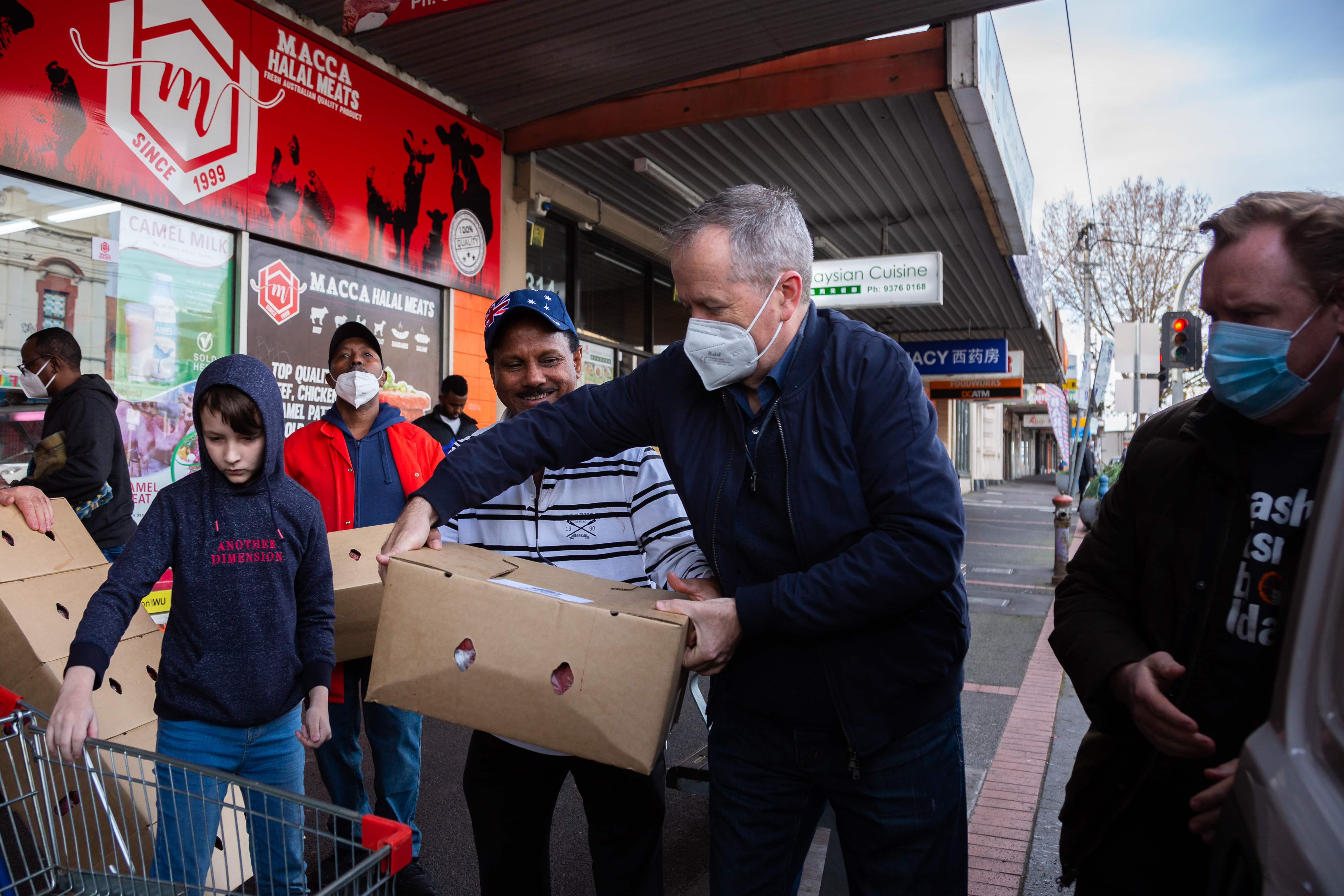 MELBOURNE, AUSTRALIA - JULY 10:  Bill Shorten (centre) and the Secretary of Victorian Trades Hall, Luke Hilakari (R) help locals load much needed halal meat into a truck bound for the residents of the locked down housing commission towers during COVID 19 on 10 July, 2020 in Melbourne, Australia. Former Federal Labor Leader Bill Shorten, along with close allies at Trades Hall help deliver Halal meat, supplied by Macca Halal Foods to the locked down housing commission towers following a COVID-19 outbreak detected inside the complex. Mr Shorten was able to use his high profile to ensure food was not turned away by police so that it would reach the residents inside. (Photo by Speed Media/Icon Sportswire)