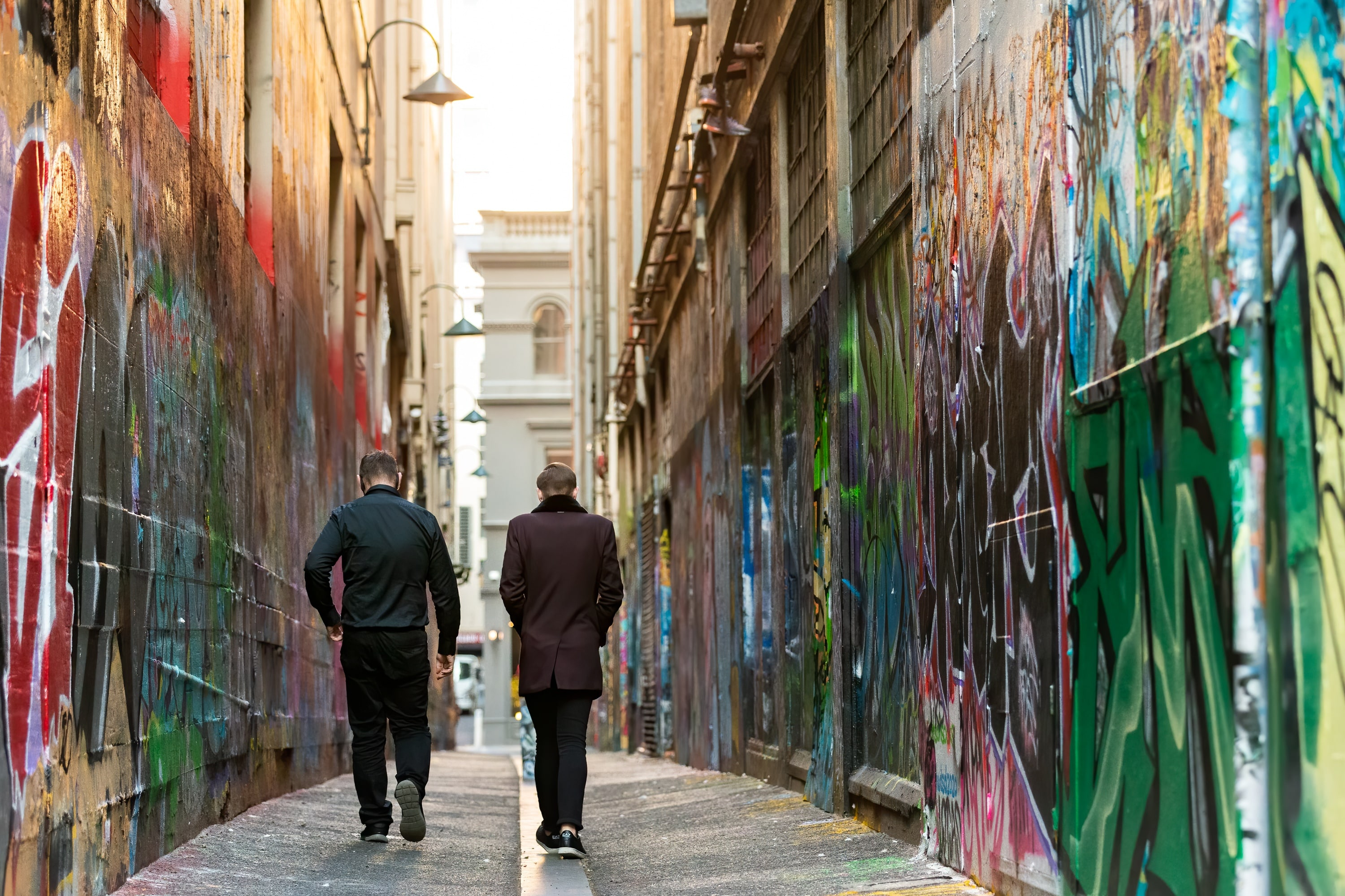 MELBOURNE, AUSTRALIA - JULY 29: Two men walk down one of Melbourne's famous alley ways during COVID 19 on 29 July, 2020 in Melbourne, Australia. As sustained high numbers of new Coronavirus cases are being discovered, Metropolitan Melbourne and the Mitchell Shire remain under Stage 3 restrictions with facemasks being made mandatory on 23 July. 295 new cases were found overnight bringing the states total active case numbers to 4,775. (Photo by Speed Media/Icon Sportswire)