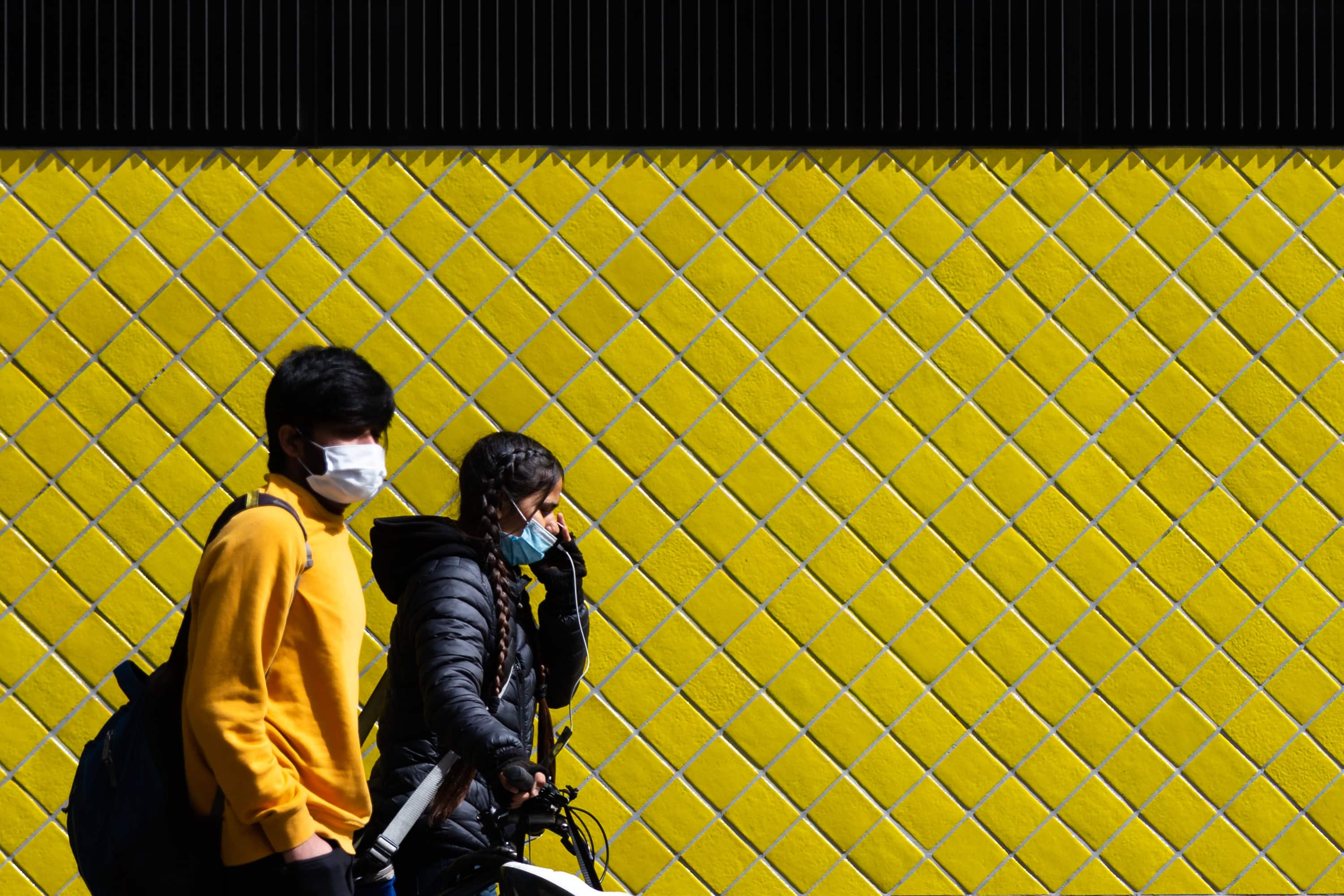 Locals are seen walking by a bright yellow tiled wall during COVID-19 in Melbourne, Australia. Victoria records a further 76 cases of Coronavirus over the past 24 hours, an increase from yesterday along with 11 deaths. This comes amid news that AstraZeneca pauses vaccine study.